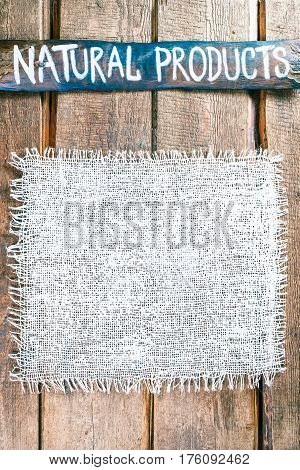 Vertical frame of white burlap on rough pine wood boards. Wooden tablet with text 'Natural products' as title bar. Structured natural style background