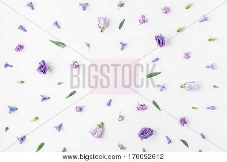 Paper blank and lilac flowers on white background. Mockup with flowers. Flat lay top view