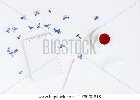 Flowers composition. Workspace with cup of tea notebook hyacinth flowers. Flat lay top view