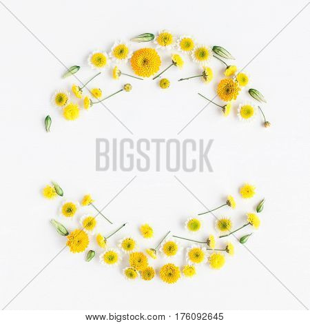 Flowers composition. Wreath made of various yellow flowers on white background. Flat lay top view