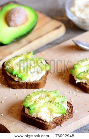 Hummus avocado sandwiches on a wooden board, avocado half. Sandwiches cooked with rye bread, fresh avocado slices, hummus and roasted sesame seeds. Vertical photo