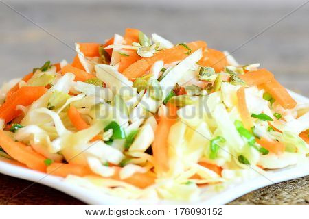 Tasty vegetable salad on a plate. Home salad with white cabbage, carrots, green onions, pumpkin seeds, lemon juice and olive oil. Simple vegetable food. Closeup