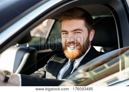 Close up portrait of a smiling bearded man in suit driving car and looking at camera