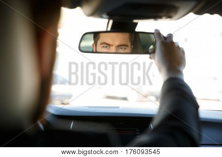 Back view of a businessman driving car and looking into rear view mirror
