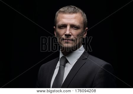 Confident businessman. Confident middle-age man in formalwear looking at camera while standing isolated on black background