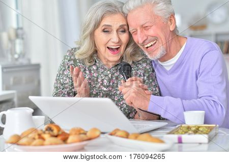 Beautiful elderly couple having breakfast with laptop