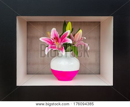Giant white and pink lily in white and pink vase stands in black and white frame, in the background brick wall under cloth. Bouquet of lilies with vase. Flowers in vase at design.