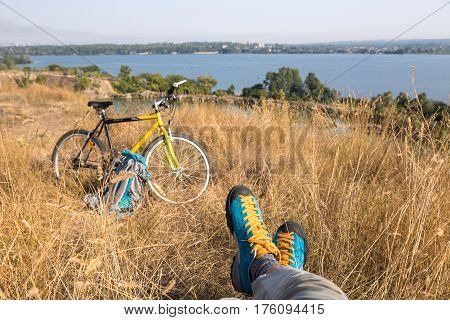 Bicyclist in bright sporty Shoes resting on yellow autumnal Grassy Lawn along with Bike Rural View on Background Sunny weather