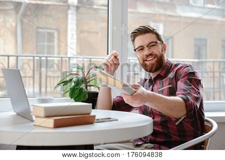 Image of happy bearded young man student sitting in cafe showing book to camera while using laptop computer. Looking at camera.