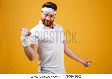 Funny sportsman which doing exercise with lightweight dumbbells and looking at camera