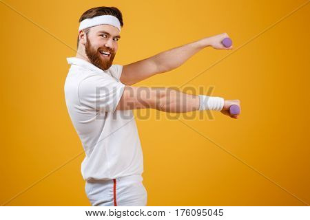 Side view of smiling sportsman which doing exercise with lightweight dumbbells while looking at camera. Isolated orange background