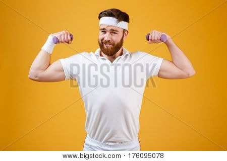 Funny retro sportsman which doing exercise with lightweight dumbbells and looking at camera. Isolated orange background