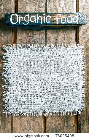 Vertical frame of white burlap on rough pine wood boards. Wooden tablet with text 'Organic food' as title bar. Structured natural style background