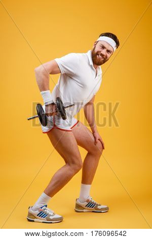 Side view of smiling sportsman doing exercise with dumbbell. Full length portrait over orange background
