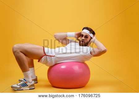 Side view of sportsman which lying on fitness ball and looking at camera. Isolated orange background