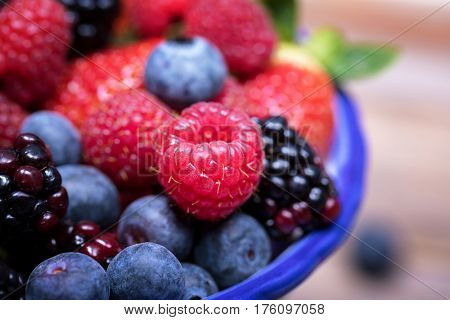 Closeup view of summer fruits in a blue-rimmed ceramic bowl, with blueberries, strawberries, raspberries and blackberries.