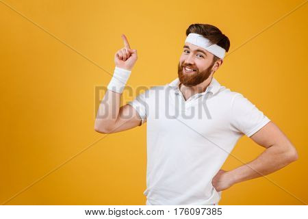 Smiling sportsman which holding arm at hip and pointing up while looking at camera. Isolated orange background
