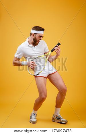 Vertical image of Funny sportsman in sunglasses which playing on tennis racquet. Full length portrait over orange background