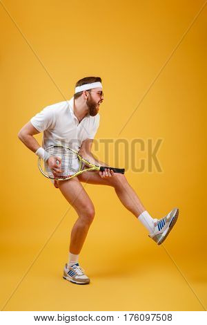 Vertical image of bearded sportsman in sunglasses which playing on the tennis racquet. Full length portrait over orange background