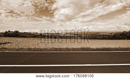 Asphalt Road between Autumn Plowed Fields in the Tuscany Vintage Style Sepia