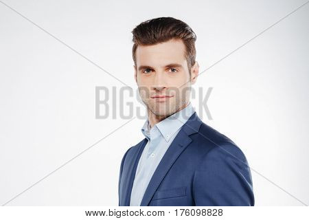 Business man which standing sideways and looking at camera