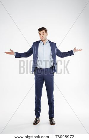 Full length portrait of Incomprehensible business man which posing in studio and looking at camera. Isolated white background