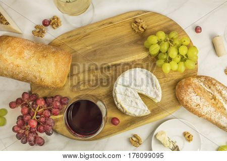 An overhead photo of glasses of wine with cheese, white and rye bread, purple and white grapes, and walnuts, at a wine pairing, with a place for text