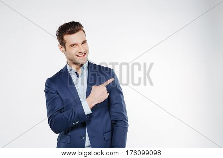 Smiling business man which pointing away and looking at camera. Isolated white background