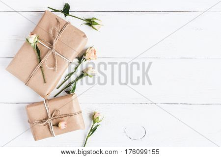 Gift and rose flowers on wooden white background. Top view flat lay