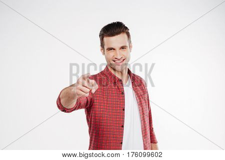 Smiling man in shirt which pointing at camera. Isolated white background