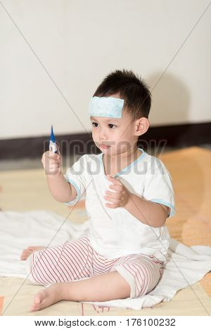 Asian Boy Having Fever .  Kid Attach Cooling Gel Pad On His Forehead For Relief Fever
