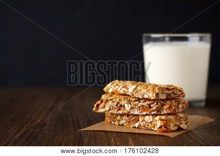 Healthy granola bars on parchment with milk on wooden table. Copy space.