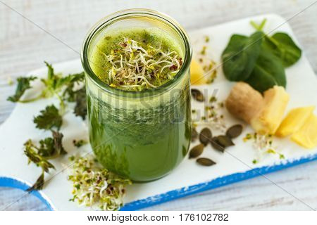 Homemade green smoothie made from pineapple juice, spinach, nettle, seeds and bean sprouts