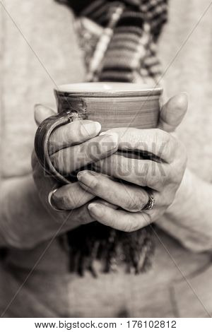 Monochrome Close Up Of Pensioners Hands Cupping Hot Drink.