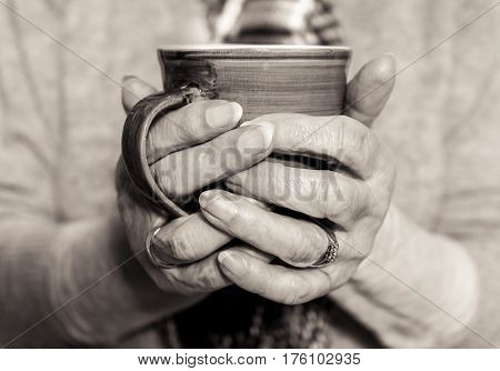 Elderly Woman's Hands Holding A Hot Drink. Monochrome.