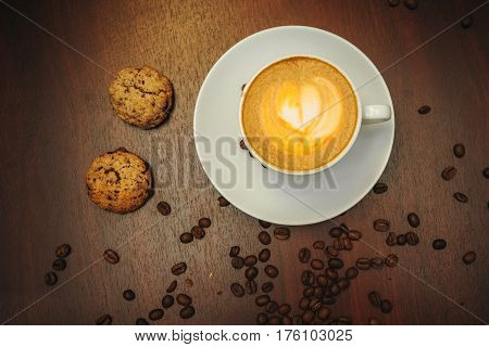 Cup of coffee to go on the wooden table with orange latte art. Street coffee. Top View. Color