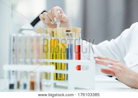 Close-up partial view of female scientist working with test tubes in chemical laboratory