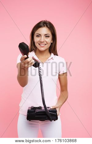 Pretty young woman in casual outfit makes phonecalls and holds receiver isolated on pink background