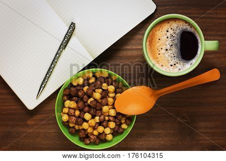 Planning the day or educating while having healthy breakfast of two varieties corn cereals and fresh coffee