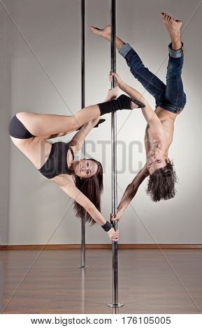 Young couple of pole dancers stopped in acrobatic position on the pylon