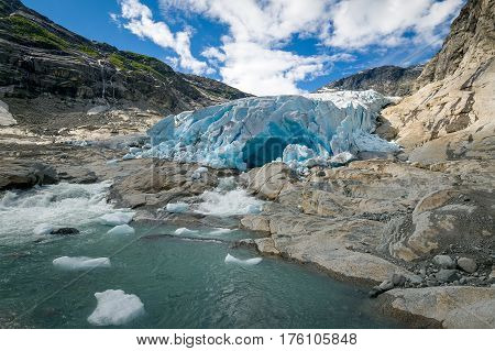 Wide angle view of Nigardsbreen Glacier ice, blue cave and melted water lake. Popular Norway landmark and national park.