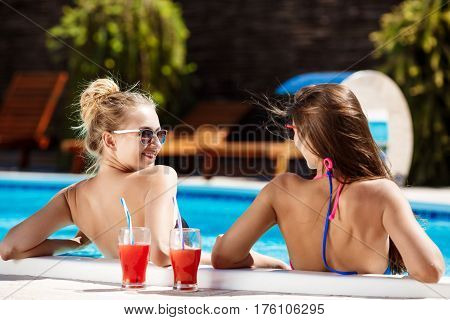 Young beautiful girls in swimwear smiling, speaking, relaxing in swimming pool. Copy space.