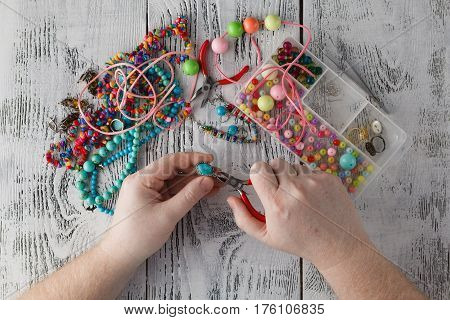 Man Making Handmade Jewelry. Boxes With Beads, Accessories For Needlework On White Wooden Table. Han