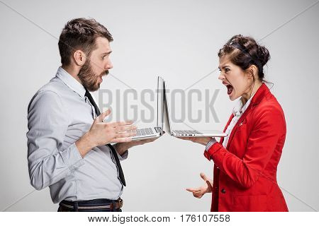 The furiously screaming young businessman and businesswoman with laptops on gray background. The concept of relationship of colleagues.