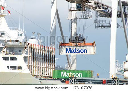 Oakland CA - March 06 2016: Matson cargo ship MAHIMAHI loading at the Port of Oakland. Crane operators can move an average of 30 containers per hour on or off the ships.