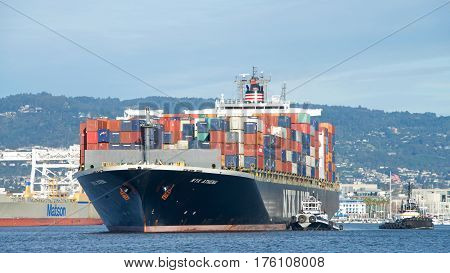 Oakland CA - March 07 2017: Tugboats assist Cargo ship NYK ATHENA to maneuver into the Port of Oakland. Nippon Yusen Kabushiki Kaisha (NYK) is one of the oldest and largest shipping companies in the world.