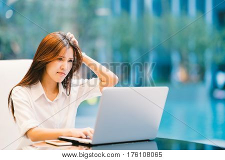 Asian woman working with laptop at home or modern office. Serious confused or frustrated expression. With copy space.