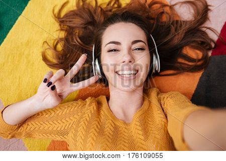 Top view of a smiling pretty girl in headphones showing peace gesture while lying on a carpet at home and taking selfie