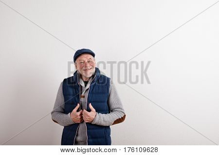 Handsome senior man in gray sweater, blue vest jacket and flat cap smiling. Studio shot against white wall.