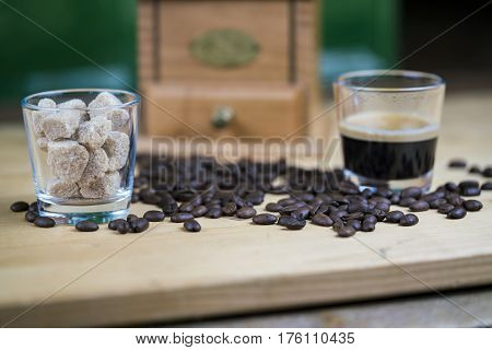 Fresh roasted coffee beans with a glass of espresso and sugar cubes in a low angle view on a wooden kitchen table